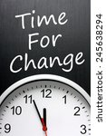 Small photo of The phrase Time For Change written on a blackboard above a modern clock with the time at almost midnight or high noon