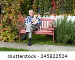 Stock photo senior man hugging his dog on his lap on bench 245822524