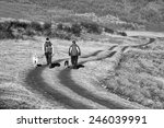 Two Man And Dog Walk On Dirt...