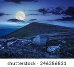 composite landscape with white sharp boulders on the hillside near mountain peak at night in fulll moon light - stock photo