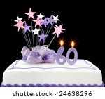 Fancy cake with number 60 candles.  Decorated with ribbons and star-shapes, in pastel tones on black background. - stock photo