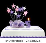 Fancy cake with number 5 candle.  Decorated with ribbons and star shapes, in pastel tones over black background. - stock photo