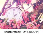 Small photo of Set your clocks back in spring with this whimsical image of a clock surrounded by spring flowers set to 2 o clock! Extreme shallow depth of field with selective focus on clock.