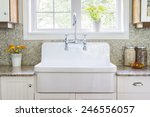 Stock photo kitchen interior with large rustic white porcelain sink and granite stone countertop under sunny 246556057