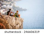 Young couple sitting on rock and enjoying beautiful view