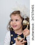Small photo of Cute young girl wearing a blue dress with gold spots and alice band with a white bow talking on the retro telephone