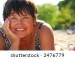 Portrait of a mature woman lying on a sandy beach - stock photo