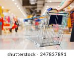 woman pushing shopping cart in...