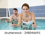 Couple In Pool Doing Aquabike...