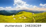 composite landscape with narrow meadow path in grass among white stones on top of mountain range in morning light with rainbow - stock photo