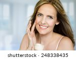 woman is applying cream to her... | Shutterstock . vector #248338435