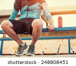 Stock photo sportsman with a bottle of water sitting and resting at the railing at the stadium 248808451