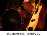 Drum kit and guitar in subdued stage lighting. - stock photo
