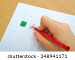 child drawing red triangle and