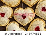 Heart shaped cherry hand pies on wooden table tied with red and white bakers twine