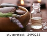 bottle of essential oil, massage stones,candles,lavender and bath-salt in a tight composition - stock photo
