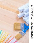 Small photo of white blueprints color sampler and two paintbrushes with blue handles on wooden board with copysapce