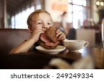 Little Boy In A Cafe During...