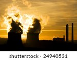 industrial landscape of power station at sunset ommitting pollution into evening sky - stock photo
