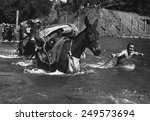 American soldiers lead pack mules through a swift river enroute to Bhamo, Burma. The Mule skinners were attached to 2nd Battalion, 475th Infantry, Mars Task Force, during World War 2. Nov. 17, 1944.