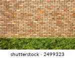 Brick wall and green grass. - stock photo
