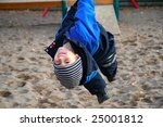 Cheerful boy playing at the playground (winter time) - stock photo