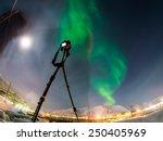 DSLR Camera on tripod shooting amazing green aurora borealis (northern lights) in moonlit night