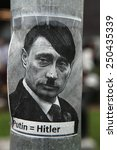 Small photo of PRAGUE, CZECH REPUBLIC - MAY 24, 2014: Sticker depicting Russian president Vladimir Putin as Adolf Hitler and with an equals sign between their names seen in Prague, Czech Republic.