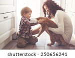 Stock photo mother with her baby playing with pet on the floor at the kitchen at home 250656241