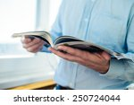 a man looks at a magazine.... | Shutterstock . vector #250724044