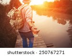 Stock photo traveler with backpack walking over wooden bridge on the lake in sunset 250767271