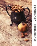 Small photo of Almonds in a coper old style vase, on old wooden table background with pomegranate