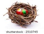Painted easter egg in bird's nest over white background - stock photo