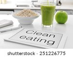 Small photo of a tablet with the text clean eating written in it and a bowl with oatmeal cereal, a glass with a green smoothie and an apple on the kitchen table