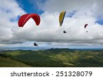 Three Paragliding Over The...