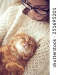 Stock photo cute ginger cat sleeps warming in knit sweater on his owner s hands 251695201