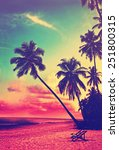 Stock photo beautiful tropical beach with silhouettes of palm trees at sunset travel background with retro 251800315
