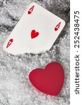 Small photo of Red heart with ace of hearts in the snow