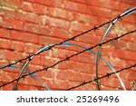Security Fence with Razor and Barb Wire against a Brick Wall - stock photo