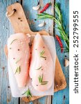 Small photo of raw chicken fillet with garlic, pepper and rosemary on a blue wooden background