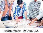 Small photo of Advertising agency team choosing model for campaign among pictures spread out on table