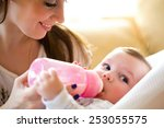 happy mother feeds the baby... | Shutterstock . vector #253055575