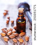Small photo of almond oil in a glass bottle with whole nuts
