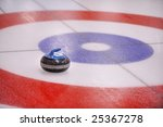 A granite 'rock' lands in the target in a game of Curling. The pebbled ice is a part of the rink preparation. - stock photo