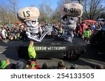 "Small photo of DUSSELDORF, GERMANY - FEBRUARY 16, 2015: A Carnival Monday (Rosenmontag) float with two skeletons named ""IS"" and ""Al-Qaida"" arm wrestling in a competition on February 16, 2015 in Dusseldorf."