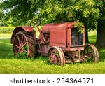 A Old Red Tractor Sits Under A...