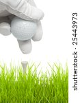 putting golf ball on a tee isolated against white background - stock photo