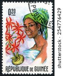 "Small photo of GUINEA - CIRCA 1966: a stamp printed in Guinea from the ""Guinean Flora and Female Headdresses "" shows Ammocharis and Woman, circa 1966."