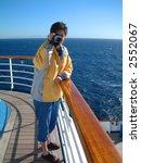Tourist woman on cruise ship wearing yellow jacket and holding video camera - stock photo