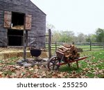 This is a shot of a firewood cart with a barn in the background. - stock photo